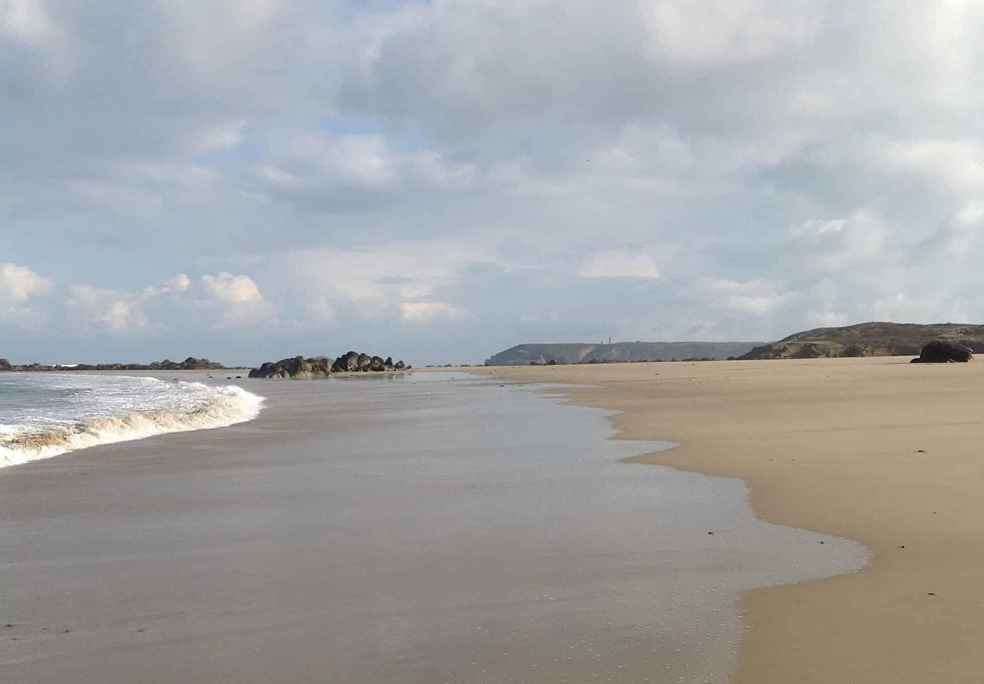 plage longue étendue rochers mer ecume calme